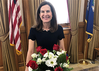 Susan Bysiewicz poses with flags and flowers