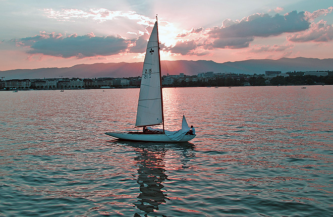 Man on sail boat off coast of Geneva
