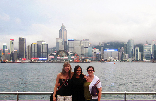 Three students with Hong Kong skyline in background