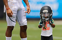 Child standing next to football player, wearing helmet