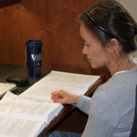 Student studying in carrel w/Duke Law mug