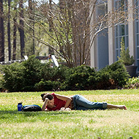student studying on lawn in front of school