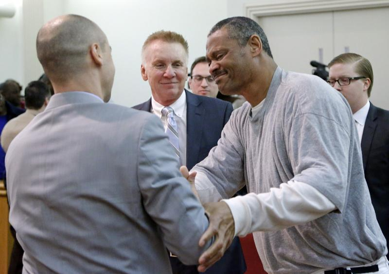 Prof. Jamie Lau '09 shaking hands with Howard Dudley. (Photo: Chris Seward, News & Observer)
