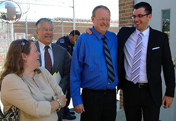 Michael Parker, second from right, is greeted on his release from prison by members of his legal team, from right: Benjamin Glover, Sean Devereux T'69, and Buffy Skolnick, Devereux's assistant