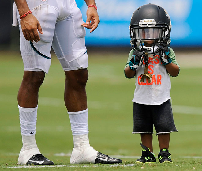 Male child on football field wearing oversize helmet, with adult football player beside him