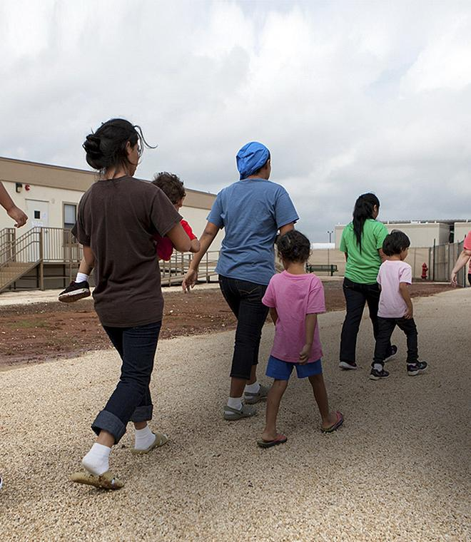 Parents and children seeking asylum walk past trailers while detained in Texas