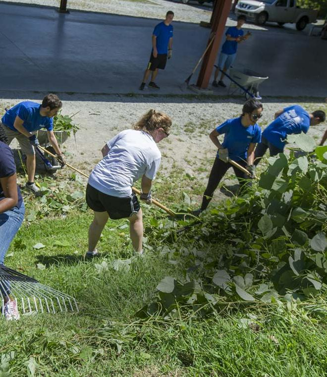 Duke Law students at public service event raking and cleaning lawns and foliage in Durham
