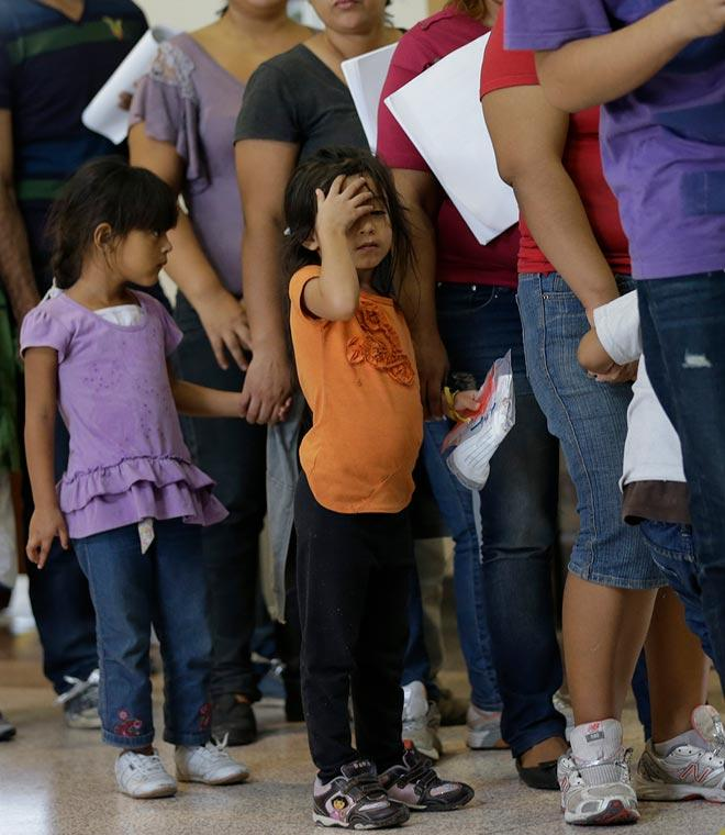 immigrants who entered the U.S. illegally stand in line for tickets at the bus station after they were released from a U.S. Customs and Border Protection processing facility in McAllen, Texas
