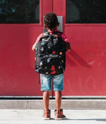 Child standing at door to school