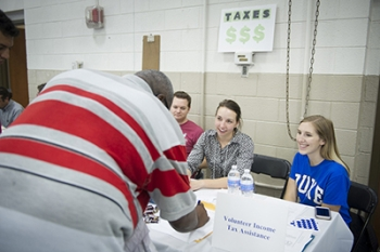 Olivia Cole '17 (far right) signs in an attendee interested in receiving information about Duke Law's Veterans Assistance Project along with Hope Standeski '17, middle, and Ric Stubbs '17, left.
